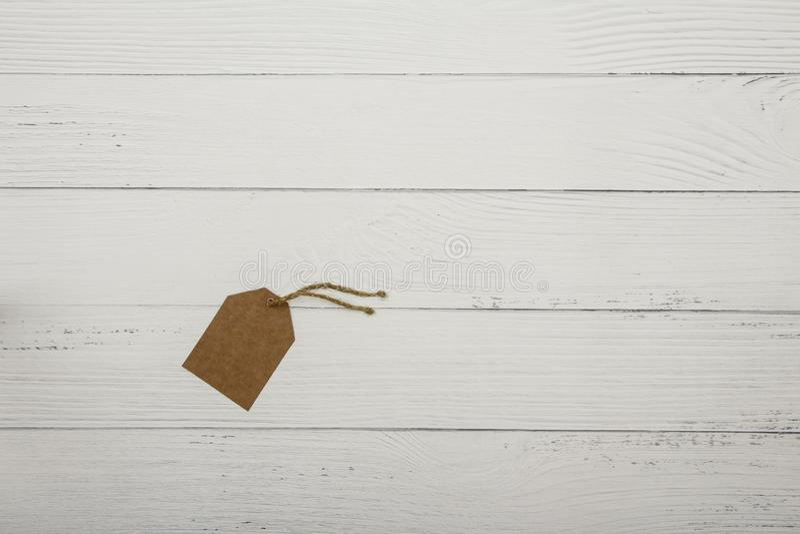 Пустой коричневый ценник на на белой деревянной предпосылке над взглядом Ценник или ярлык картона коричневого цвета пробела на бе стоковая фотография