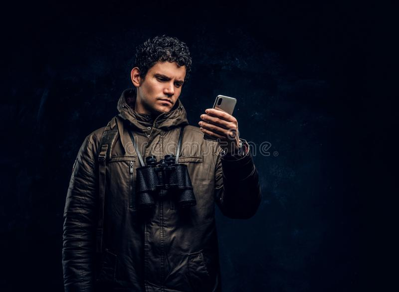 Путешественник в шестерне с биноклями использует навигацию GPS на его смартфоне в студии против темной стены стоковое фото