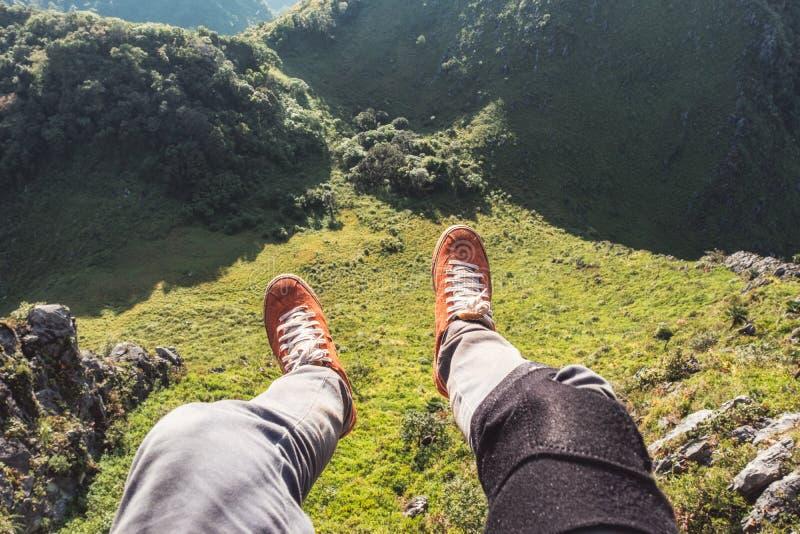 Путешественник ног ослабляя и вися на скале с вечнозеленой горой стоковые фотографии rf