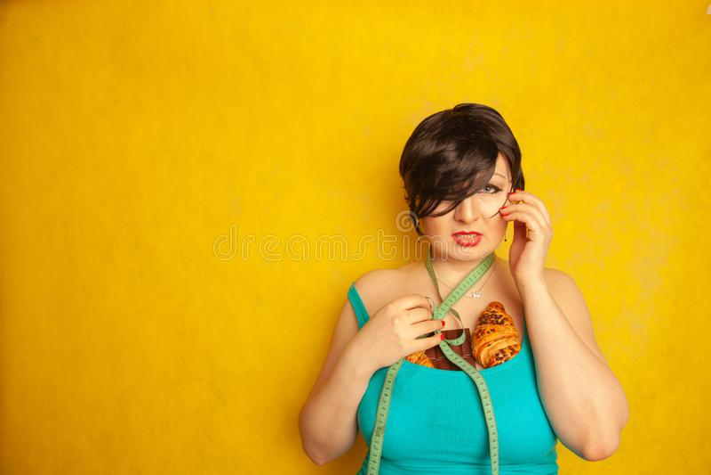Пухлая девушка несчастная с standarts моды и грустная с лентой сантиметра и едой высоко-калории, она плачет стоковое изображение