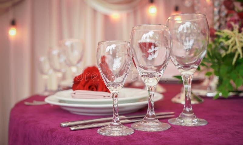 Праздничная сервировка стола свадьбы с красными цветками, салфетками, винтажным столовым прибором, стеклами и свечами, ярким офор стоковые изображения