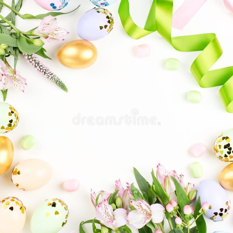 Праздничная счастливая предпосылка пасхи с украшенными яйцами, цветками, конфетой и лентами в пастельных цветах на белизне скопир стоковое изображение rf