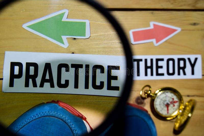 Практика или теория напротив знаков направления на увеличивать с тапкой и компасом на деревянном стоковое фото rf