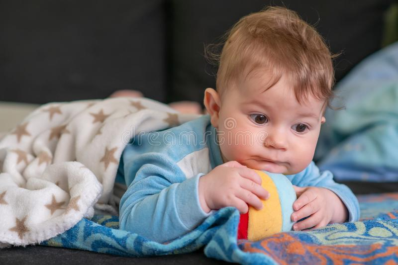 Прекрасный маленький младенец лежа на его животе и играх с пестротканым мягким шариком стоковые фото