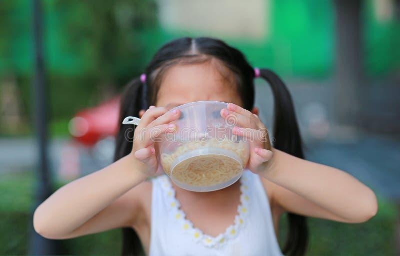 Прелестная маленькая азиатская девушка ребенк есть лапши быстрого приготовления в утре на саде стоковые изображения rf