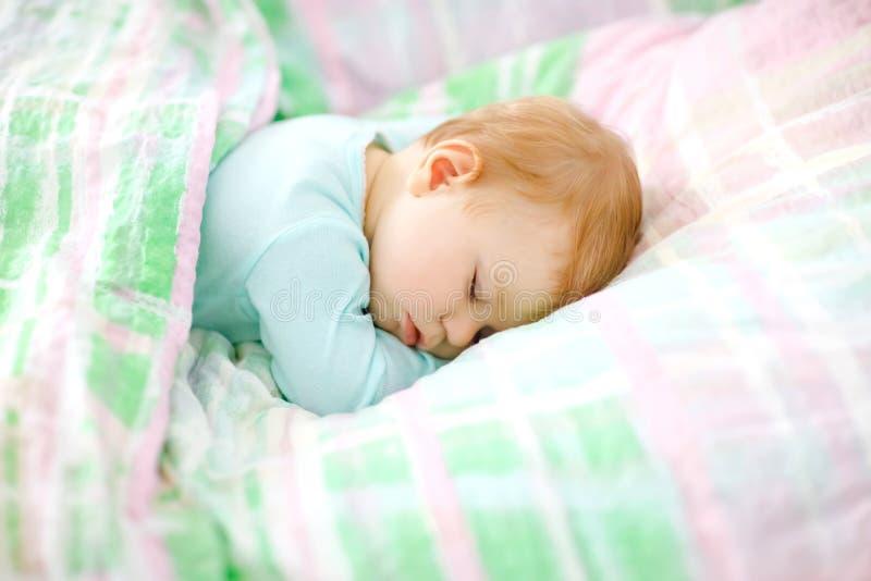 Прелестный маленький ребёнок спать в кровати Спокойный мирный ребенок мечтая во время сна дня Красивый младенец в родителях кладе стоковые фото