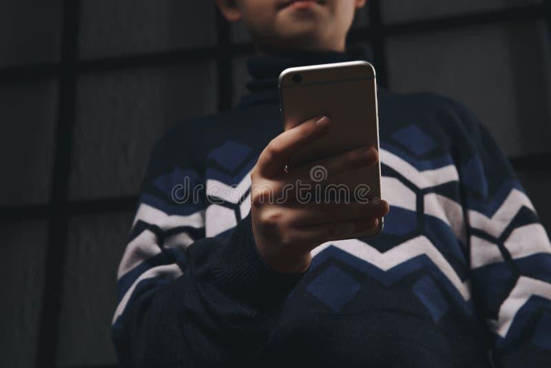 Предназначенный для подростков телефон удерживания мальчика и чувствовать грустный Жертва cyberbullying Задирать телефона стоковая фотография rf