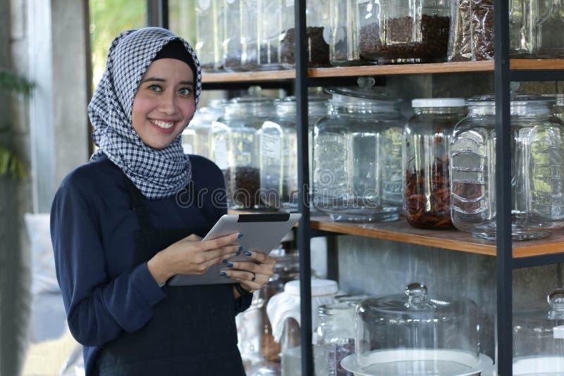 Предприниматели проверяют запас на кофе в полке опарника используя ПК планшета, бизнесмена проверяя хранение стоковые изображения