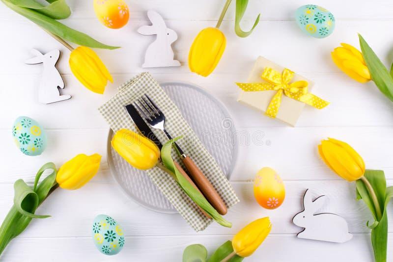 Предпосылка пасхи весны для меню Украшение пасхального яйца, зайчик, салфетка белья на плите и столовый прибор кухни на белом дер стоковое изображение