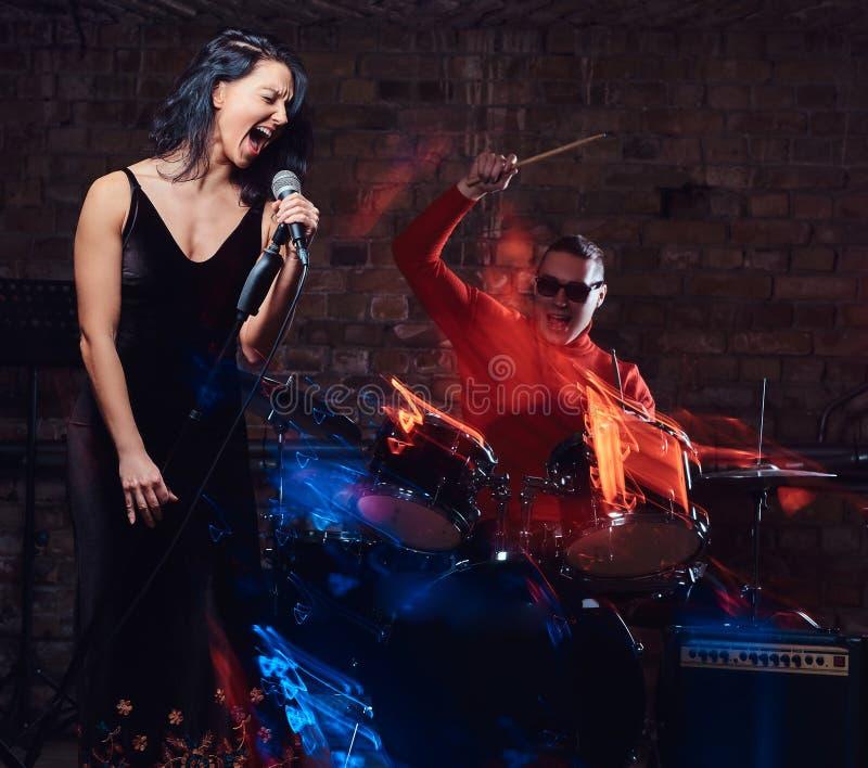Представление джаз-бэнда Соедините музыкантов - барабанщика и певицы в ночном клубе стоковые изображения