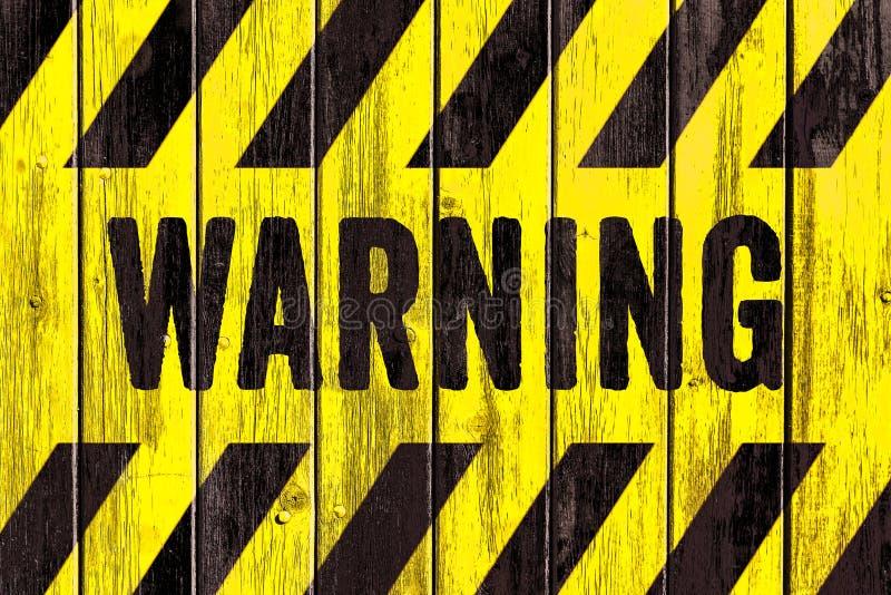 ПРЕДУПРЕЖДАЮЩИЙ текст слова знака опасности как восковка с желтыми и черными нашивками покрашенными на предпосылке деревянной тек иллюстрация штока