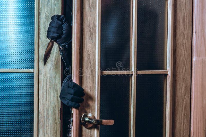 Преступник входит в дом в темноту Руки человека в черных перчатках и ноже стоковое изображение