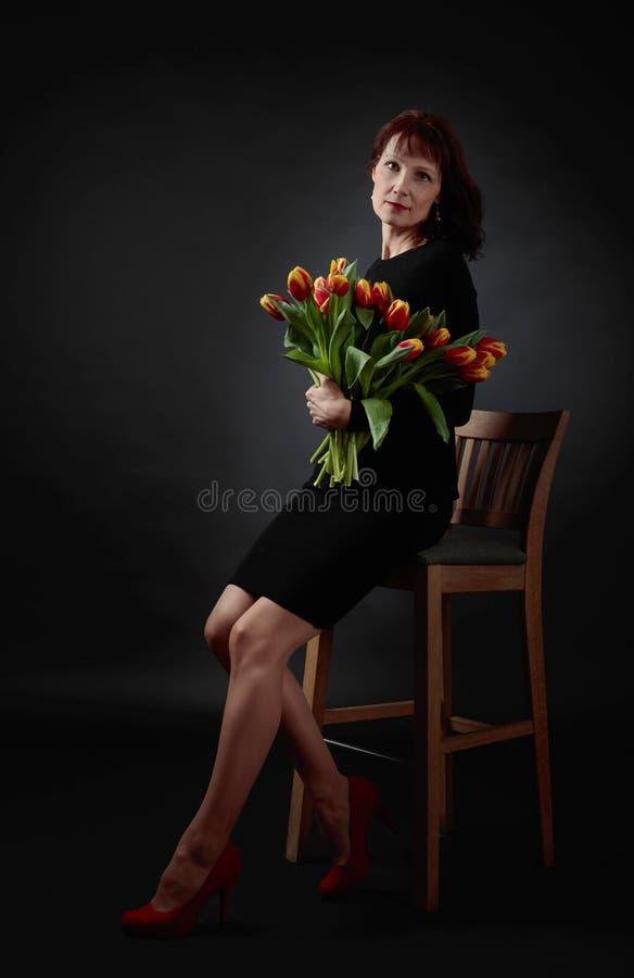 Привлекательная женщина с букетом красных и желтых тюльпанов стоковые изображения rf