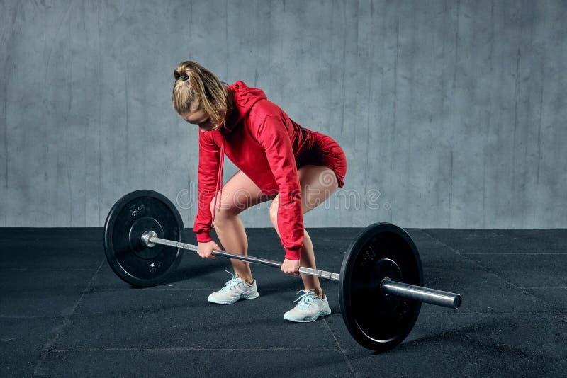 Привлекательная молодая sporty женщина разрабатывает в спортзале Мышечная женщина сидит на корточках со штангой стоковое фото rf