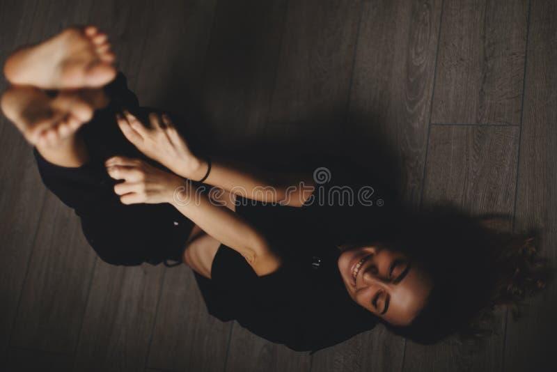 Привлекательная сексуальная женщина лежит на поле Девушка выглядит счастливой и улыбкой Женщина лежа на поле с ногами вверх стоковая фотография