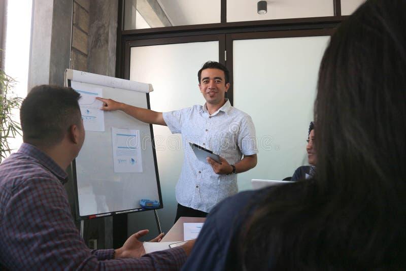 Привлекательный азиатский человек со случайным платьем представляя с белой доской во фронте его коллеж на внутри помещения офисе  стоковые фото