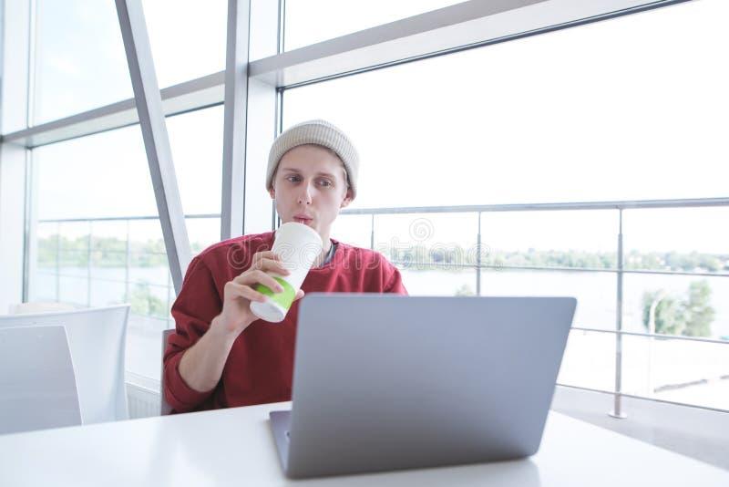 Привлекательный молодой человек в случайных одеждах сидя на таблице смотря ноутбук и выпивая холодный напиток стоковое изображение