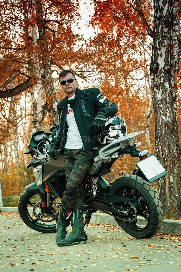 Привлекательный парень и молодая женщина в черном кожаном обмундировании с мотоциклом стоковые фотографии rf