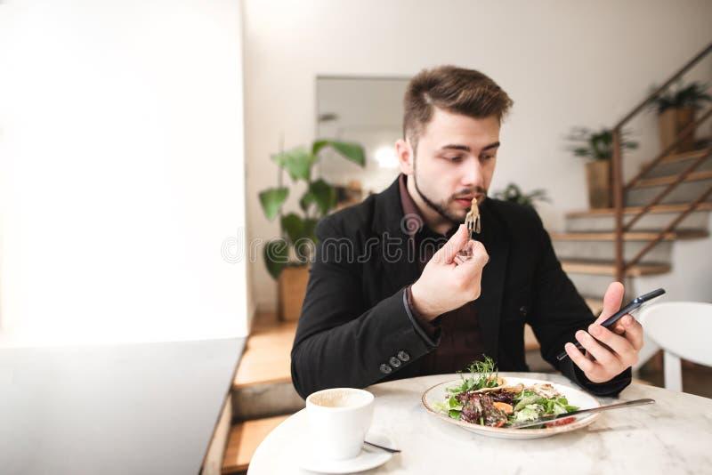Привлекательный человек в костюме сидит в уютном ресторане, есть салат с плитой и используя смартфон стоковые фото