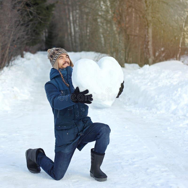 Привлекательное бородатое положение человека на колене и удержание огромного сердца сделанный снега в его руках, на парке зимы вс стоковые изображения rf