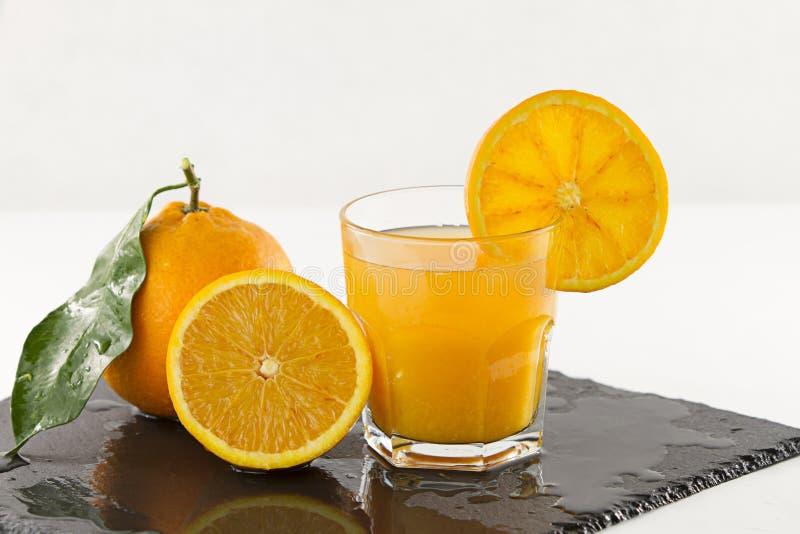 Приглашая стекло полное апельсинового сока с оранжевым куском на оправе, половинном апельсине и всем одном с лист на квадратном в стоковая фотография