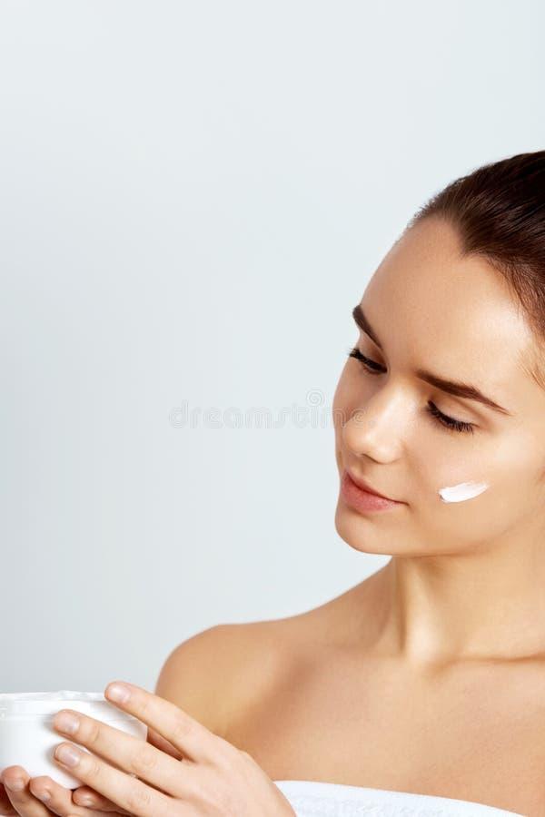 Принципиальная схема внимательности кожи Красивая сливк стороны удерживания женщины в руках Портрет крупного плана модельной деву стоковое фото