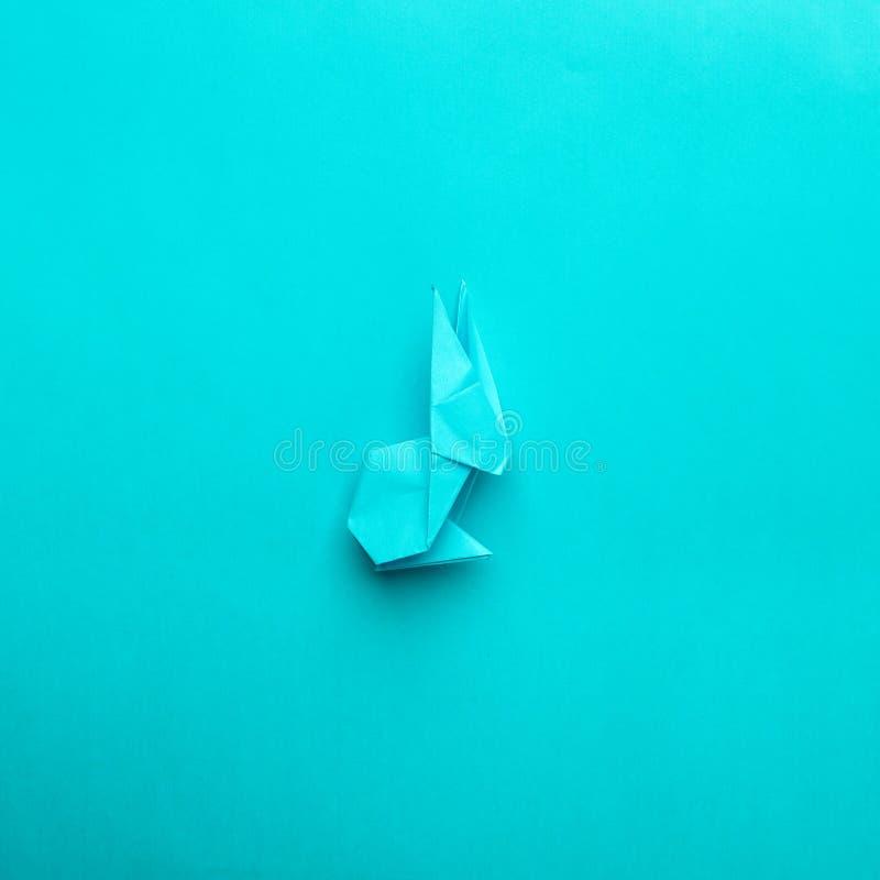 принципиальная схема пасха счастливая Плоское положение Минимальная концепция Взгляд сверху зайчик papercraft origami на голубой  стоковое изображение rf