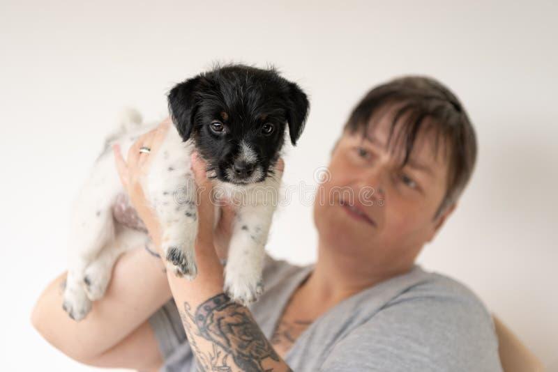 Приятельство между владельцем и его младенцем поднимает собаку домкратом щенка терьера Рассела Обработчик носит его щенок 7 5 ста стоковые фото