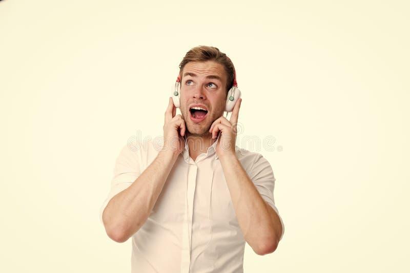 Приятная мелодия Укомплектуйте личным составом слушая любимую песню в наушниках и петь Гай с наушниками слушает музыка Удовлетвор стоковая фотография