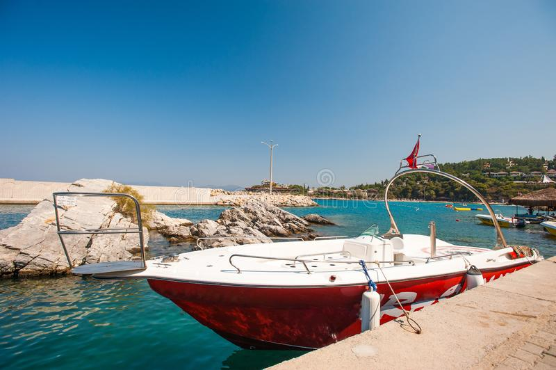 Причаленная яхта, моторная лодка Красная и белая припаркованная шлюпка стоковая фотография