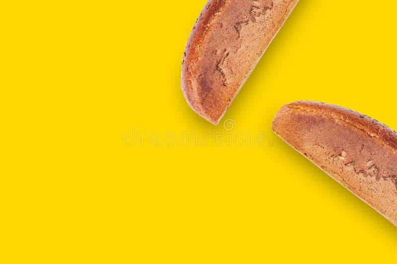 2 прямоугольных всех черных хлеба с зерном на таблице с желтым countertop на кухне скопируйте космос для вашего текста Взгляд све стоковые фото