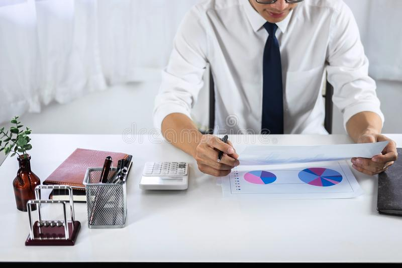 Проверка бухгалтера бизнесмена работая и высчитывать финансовые данные расхода на документах диаграммы, делая финансы в рабочем м стоковая фотография rf