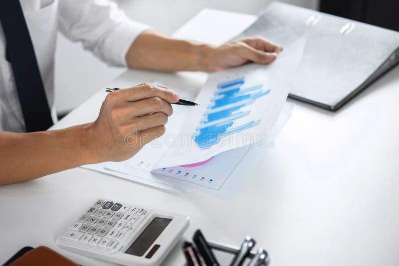 Проверка бухгалтера бизнесмена работая и высчитывать финансовые данные расхода на документах диаграммы, делая финансы в рабочем м стоковые фотографии rf