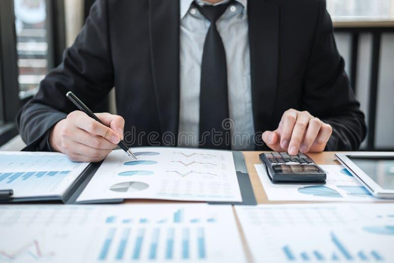 Проверка бухгалтера бизнесмена работая и высчитывать финансовые данные расхода на документах диаграммы, делая финансы в рабочем м стоковое фото rf