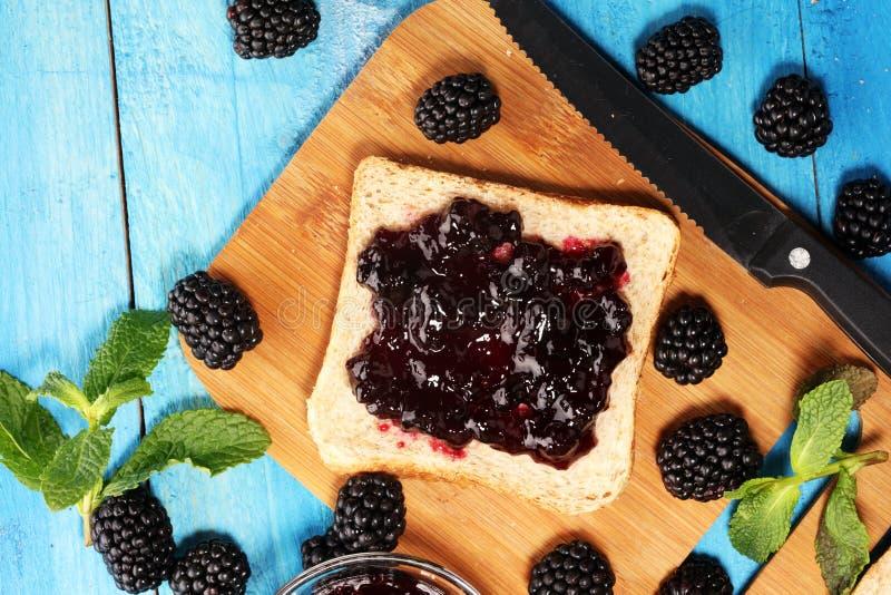 Провозглашайте тост хлеб с домодельным вареньем ежевики или мармелад на таблице служил с маслом на завтрак или завтрак-обедом стоковые фотографии rf