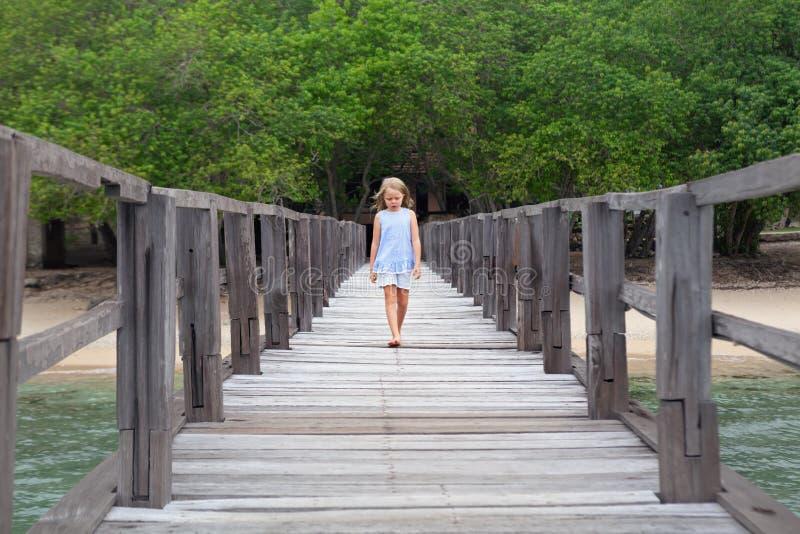 Прогулка маленькой девочки деревянной пристанью на пляже песка моря стоковые изображения rf
