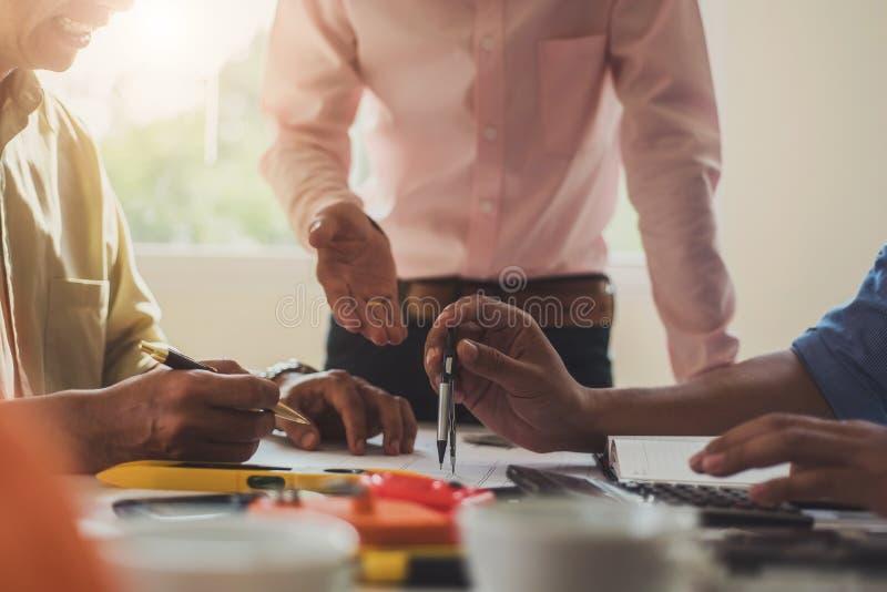 Проектируйте людей встречая работу и указывать на чертежей в офисе для обсуждать Концепция инструментов и конструкции инженерства стоковое изображение rf