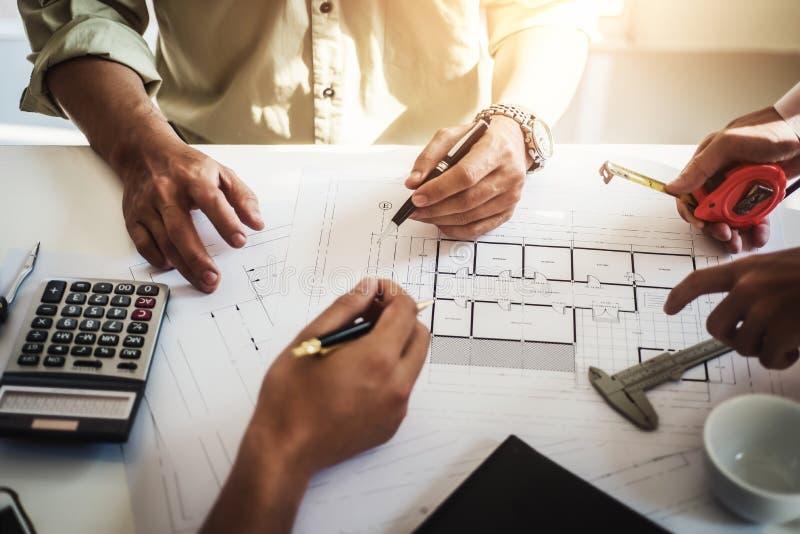 Проектируйте людей встречая работу и указывать на чертежей в офисе для обсуждать Концепция инструментов и конструкции инженерства стоковые фотографии rf