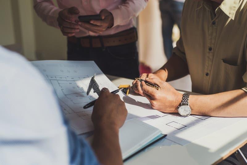 Проектируйте людей встречая работу и указывать на чертежей в офисе для обсуждать Концепция инструментов и конструкции инженерства стоковая фотография