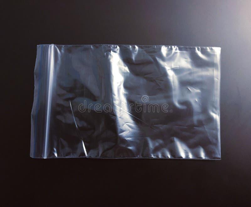Прозрачная сумка пакета полиэтилена на темной предпосылке стоковые изображения