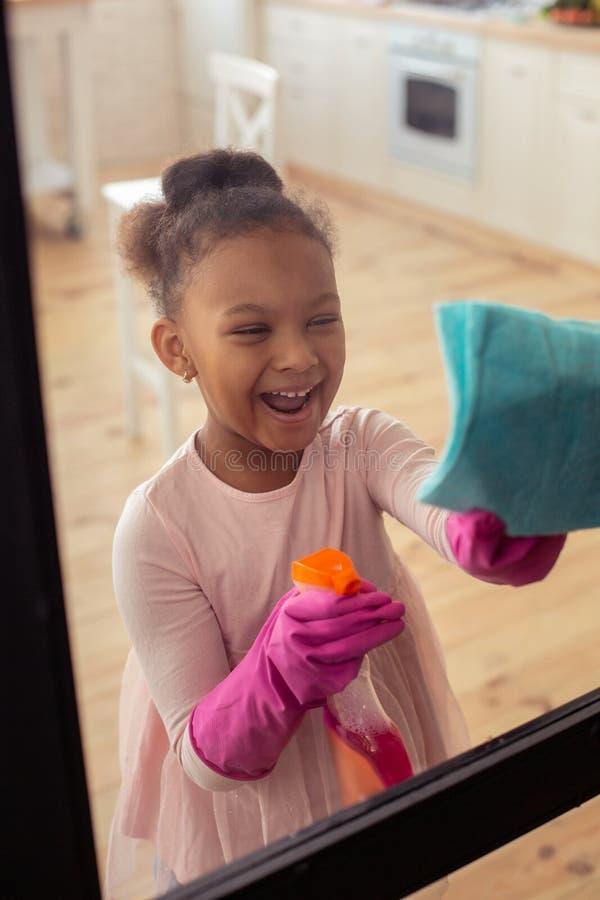 Промежуток времени смешной девушки смеясь наслаждаясь помогающ ее матери с чисткой стоковое фото rf