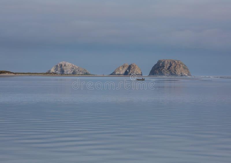 Пропуски лодочника и рыболова перед 3 сдобренными утесами стоковые фотографии rf