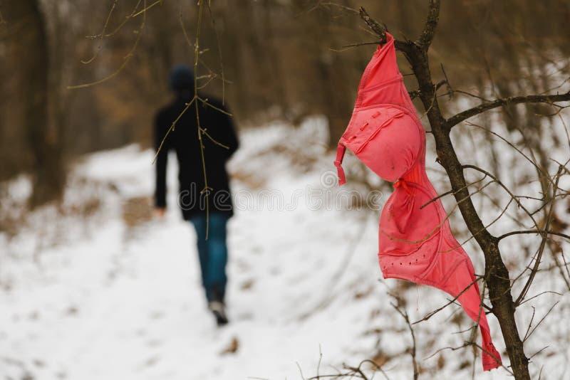 Проституция - красный бюстгальтер в лесе - молодой человек на заднем плане стоковое фото rf