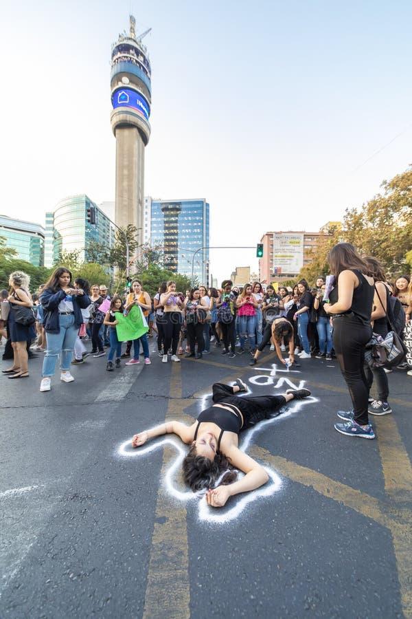 Протестующий девушки лежа на асфальте улицы на Международном женском дне 8-ое марта на улицах центра города Сантьяго, Чили стоковая фотография