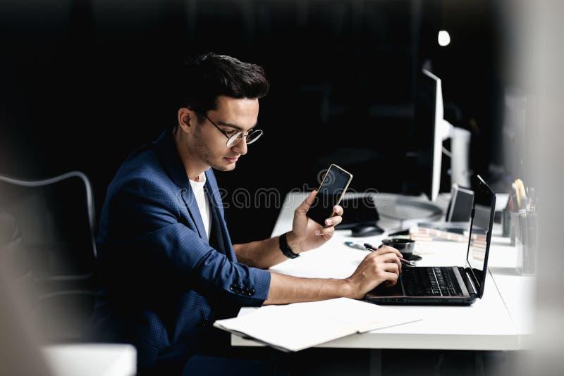 Профессиональный архитектор одетый в деловом костюме говоря по телефону и работах на ноутбуке в офисе стоковые изображения rf