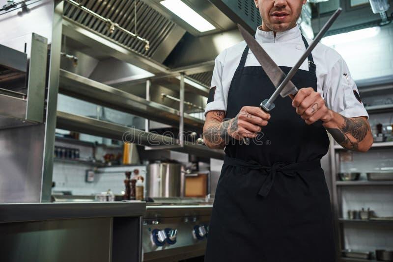 Профессиональный шеф-повар Зверский молодой человек в рисберме с несколькими татуировок на его оружиях точить нож в кухне рестора стоковое фото