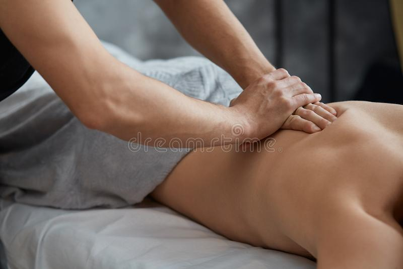 Профессиональный терапевт массажа обрабатывает мужского пациента в квартире стоковые изображения