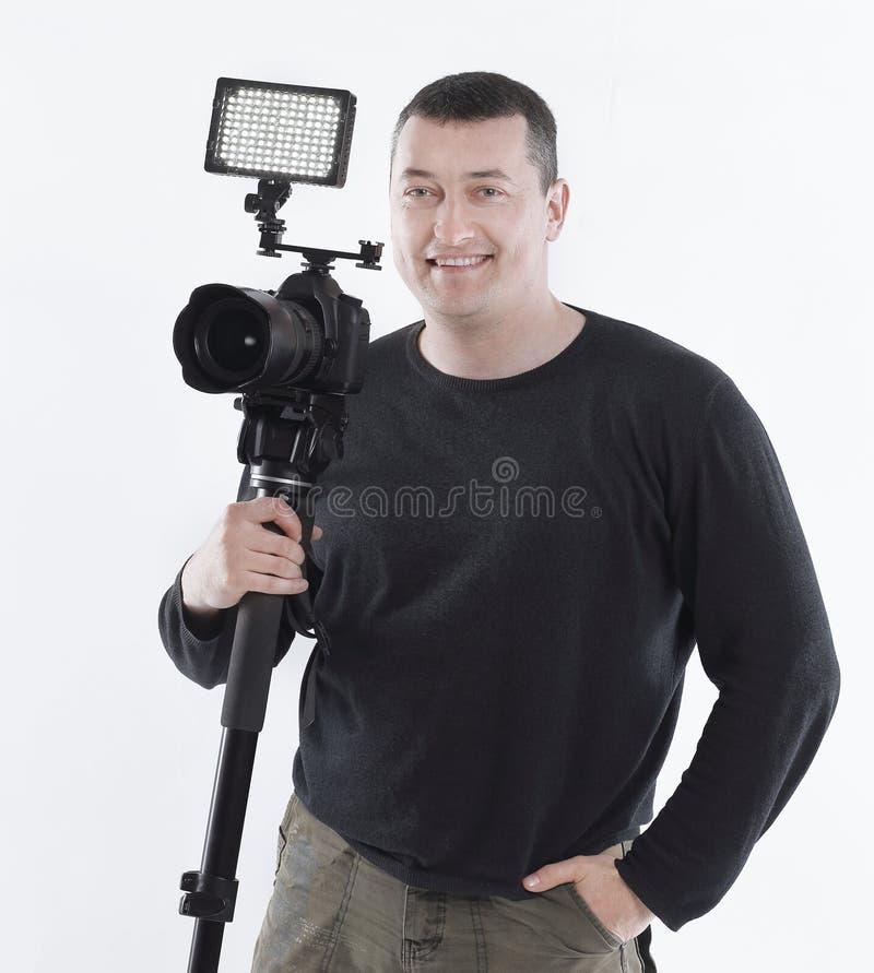 Профессиональный фотограф стоя около треноги Изолировано на белизне стоковые фотографии rf