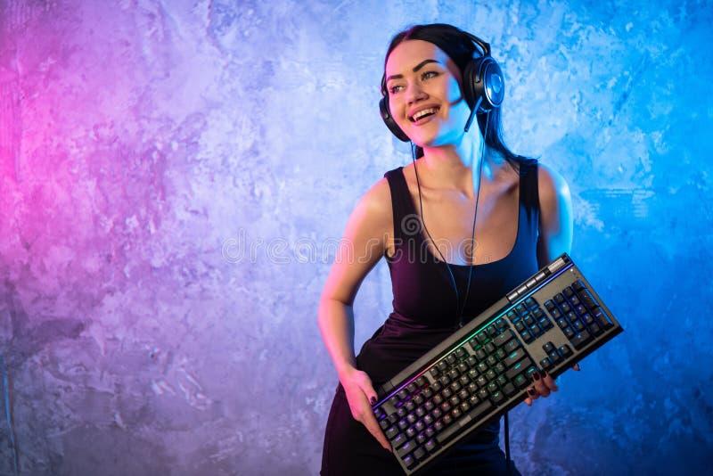 Профессиональный Gamer девушки в видеоигре стратегии MMORPG Она она представляя над красочной голубой и розовой предпосылкой с a стоковое изображение rf