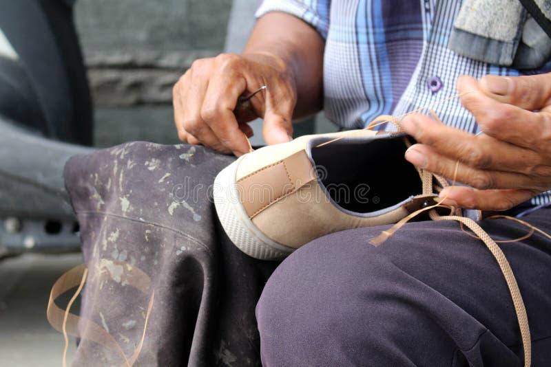 Процесс ручной репарации, подошвы и ранта ботинка фиксируя и шить стоковое изображение rf